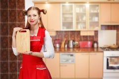 Ελκυστική χαμογελώντας νοικοκυρά στην κόκκινη ποδιά με τα αστεία ponytails α Στοκ Φωτογραφίες
