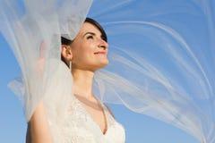 Ελκυστική χαμογελώντας νύφη με το πετώντας πέπλο Στοκ Εικόνα
