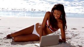Ελκυστική χαλάρωση γυναικών με το lap-top της στην παραλία φιλμ μικρού μήκους