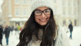 Ελκυστική όμορφη κυρία που θέτει και που φλερτάρει στη κάμερα πέρα από το χιονώδες υπόβαθρο πόλεων απόθεμα βίντεο