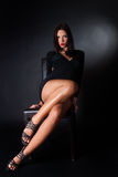 Ελκυστική brunette συνεδρίαση φορεμάτων ένδυσης μαύρη στην καρέκλα δέρματος Στοκ Εικόνες