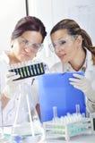 Ελκυστικοί νέοι επιστήμονες σπουδαστών PHD που παρατηρούν τη μετατόπιση χρώματος μετά από το destillation λύσης στο χημικό εργαστ Στοκ Φωτογραφία