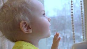 Ελκυστικός λίγο κοριτσάκι που φαίνεται έξω το παράθυρο 4K UltraHD, UHD απόθεμα βίντεο