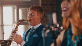 Ελκυστικός αοιδός τζαζ που αποδίδει στη σκηνή με το saxophonist στο μπλε κοστούμι ζήστε φιλμ μικρού μήκους