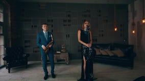 Ελκυστικός αοιδός τζαζ στο καμμένος φόρεμα που αποδίδει στη σκηνή με το saxophonist φιλμ μικρού μήκους