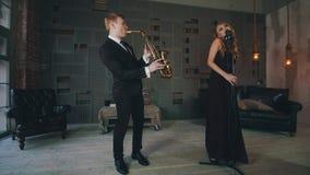 Ελκυστικός αοιδός τζαζ στο μαύρο φόρεμα που αποδίδει στη σκηνή με το saxophonist φιλμ μικρού μήκους