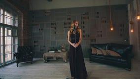 Ελκυστικός αοιδός τζαζ στο μαύρο φόρεμα που αποδίδει στο ξύλινο στάδιο στο μικρόφωνο φιλμ μικρού μήκους