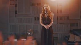 Ελκυστικός αοιδός τζαζ στο μαύρο φόρεμα στη σκηνή στο μικρόφωνο saxophonist φιλμ μικρού μήκους
