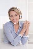Ελκυστικός βοηθός στο γραφείο με το ακουστικό. Στοκ Φωτογραφία