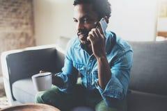 Ελκυστικός γενειοφόρος αφρικανικός επιχειρηματίας που χρησιμοποιεί το smartphone καθμένος στον καναπέ στο σπίτι του Έννοια των νέ Στοκ Φωτογραφίες