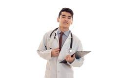 Ελκυστικός γιατρός νεαρών άνδρων σε ομοιόμορφο με το stethoscop στο λαιμό του με τον πίνακα στα χέρια του που κοιτάζουν και που θ Στοκ φωτογραφία με δικαίωμα ελεύθερης χρήσης