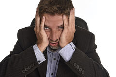 Ελκυστικός επιχειρηματίας που υφίσταται την πίεση εργασίας και τον πονοκέφαλο που κρατούν το κεφάλι του κουρασμένο και ανησυχημέν Στοκ Φωτογραφία