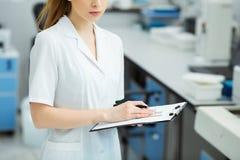 Ελκυστικός εργαζόμενος εργαστηρίων θηλυκών που κάνει τη ιατρική έρευνα στο σύγχρονο εργαστήριο Φάκελλος εγγράφων εκμετάλλευσης επ Στοκ Εικόνες