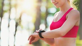 Ελκυστικός θηλυκός αθλητής που χρησιμοποιεί την ικανότητα app στο έξυπνο ρολόι της που ελέγχει workout Στοκ Εικόνες