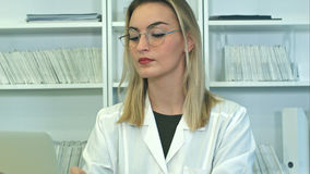 Ελκυστικός θηλυκός γιατρός στα γυαλιά που χρησιμοποιούν τη συνεδρίαση lap-top στο γραφείο υποδοχής Στοκ φωτογραφία με δικαίωμα ελεύθερης χρήσης