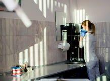 Ελκυστικός θηλυκός οδοντίατρος που στέκεται στο γραφείο του, που κοιτάζει Στοκ Εικόνα