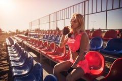 Ελκυστικός θηλυκός δρομέας που κάθεται στην παραλία που στηρίζεται μετά από το εντατικό παιχνίδι πετοσφαίρισης, το θερινό υπόβαθρ Στοκ φωτογραφία με δικαίωμα ελεύθερης χρήσης