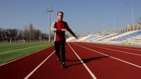Ελκυστικός κατάλληλος ενεργός νεαρός άνδρας που περπατά κάνοντας το κοντόχοντρο θερμαίνοντας υπαίθριο στάδιο μυών τεντώματος work απόθεμα βίντεο
