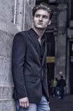 Ελκυστικός μπλε eyed, ξανθός νεαρός άνδρας που κλίνει ενάντια στον άσπρο τοίχο Στοκ φωτογραφία με δικαίωμα ελεύθερης χρήσης