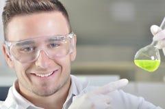 Ελκυστικός νέος επιστήμονας σπουδαστών PHD που παρατηρεί τη μετατόπιση χρώματος μετά από το destillation λύσης στο χημικό εργαστή Στοκ Εικόνες