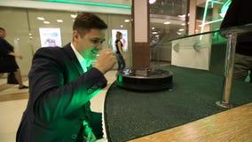 Ελκυστικός νέος επιχειρηματίας που έχει τη διασκέδαση με τη μηχανή ηλεκτρικών σκουπών φιλμ μικρού μήκους
