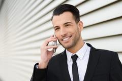 Ελκυστικός νέος επιχειρηματίας στο τηλέφωνο σε ένα κτίριο γραφείων Στοκ φωτογραφία με δικαίωμα ελεύθερης χρήσης