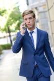 Ελκυστικός νέος επιχειρηματίας στο τηλέφωνο στο αστικό υπόβαθρο Στοκ Εικόνες