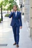 Ελκυστικός νέος επιχειρηματίας στο τηλέφωνο στο αστικό υπόβαθρο Στοκ Φωτογραφία