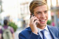 Ελκυστικός νέος επιχειρηματίας στο τηλέφωνο στο αστικό υπόβαθρο Στοκ Φωτογραφίες