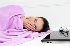 Ελκυστικός νέος ύπνος γυναικών στο κρεβάτι με το lap-top Στοκ Φωτογραφίες
