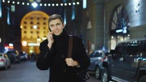 Ελκυστικός νεαρός άνδρας που μιλά σε μια οδό βραδιού, που μιλά στο τηλέφωνο φιλμ μικρού μήκους