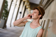 Ελκυστικός νεαρός άνδρας που φορά το καπέλο που μιλά στο κινητό τηλέφωνο Στοκ φωτογραφία με δικαίωμα ελεύθερης χρήσης