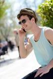 Ελκυστικός νεαρός άνδρας που φορά το καπέλο που μιλά στο κινητό τηλέφωνο Στοκ εικόνα με δικαίωμα ελεύθερης χρήσης