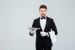 Ελκυστικός οικονόμος στο σμόκιν που στέκεται και που κρατά τον ασημένιο κενό δίσκο στοκ φωτογραφία