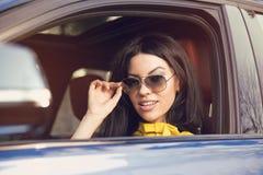 Ελκυστικός οδηγός γυναικών με τα γυαλιά ηλίου που κάθεται μέσα στο αυτοκίνητό της στοκ φωτογραφίες