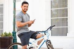 Ελκυστικός ποδηλάτης που χρησιμοποιεί ένα smartphone Στοκ φωτογραφία με δικαίωμα ελεύθερης χρήσης