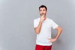 Ελκυστικός στοχαστικός νεαρός άνδρας στο άσπρο κοίταγμα πουκάμισων Στοκ Εικόνες