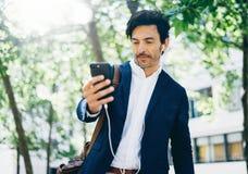 Ελκυστικός χαμογελώντας επιχειρηματίας που χρησιμοποιεί το smartphone για η μουσική περπατώντας στο πάρκο πόλεων Οριζόντιος, θολω Στοκ φωτογραφία με δικαίωμα ελεύθερης χρήσης