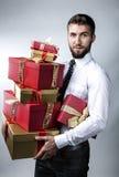 Ελκυστικό άτομο με διάφορες συσκευασίες δώρων Στοκ φωτογραφία με δικαίωμα ελεύθερης χρήσης