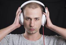 Ελκυστικό άτομο που ακούει με προσήλωση τη μουσική στα ακουστικά Στοκ φωτογραφία με δικαίωμα ελεύθερης χρήσης