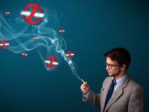 Ελκυστικό άτομο που καπνίζει το επικίνδυνο τσιγάρο με τα σημάδια απαγόρευσης του καπνίσματος Στοκ Εικόνες