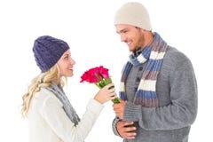 Ελκυστικό άτομο στη χειμερινή μόδα που προσφέρει τα τριαντάφυλλα στη φίλη Στοκ Φωτογραφίες