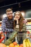 Ελκυστικό αγαπώντας ζεύγος που στέκεται κοντά στο καροτσάκι αγορών Στοκ φωτογραφία με δικαίωμα ελεύθερης χρήσης