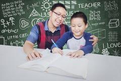 Ελκυστικό αγόρι που μελετά στην κατηγορία με το δάσκαλο Στοκ Εικόνα