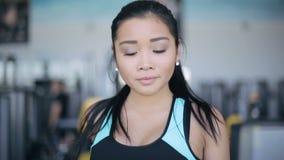 Ελκυστικό ασιατικό κορίτσι που τρέχει treadmill στη γυμναστική Πλήρες πορτρέτο προσώπου φιλμ μικρού μήκους