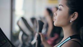 Ελκυστικό ασιατικό κορίτσι στη γυμναστική που ασκεί στη μηχανή διηθητήρων Πυροβολισμός προσώπου σχεδιαγράμματος φιλμ μικρού μήκους