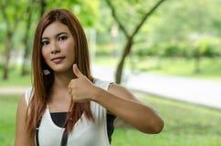 Ελκυστικό ασιατικό δόσιμο γυναικών αντίχειρες επάνω στοκ εικόνα