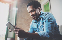 Ελκυστικό γενειοφόρο αφρικανικό άτομο που χρησιμοποιεί την ταμπλέτα για τις ειδήσεις πρωινού ανάγνωσης στο σπίτι Άνθρωποι έννοιας Στοκ Φωτογραφία