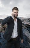Ελκυστικό επιχειρησιακό άτομο που τηλεφωνιέται σε μια έρημο πετρών Στοκ φωτογραφίες με δικαίωμα ελεύθερης χρήσης