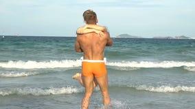 Ελκυστικό εύθυμο ζεύγος που περπατά στην παραλία Αγκάλιασμα μεταξύ τους και φιλί απόθεμα βίντεο